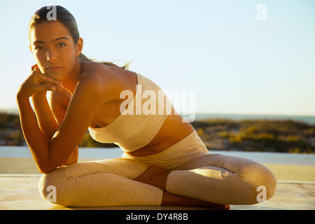 Young Woman Sitting with Legs Crossed Leaning to one side - Stock Photo