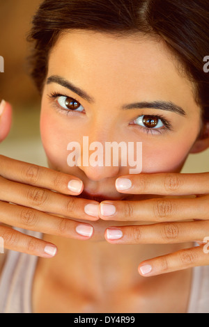 Woman with Hands Covering Mouth, Close-up View - Stock Photo