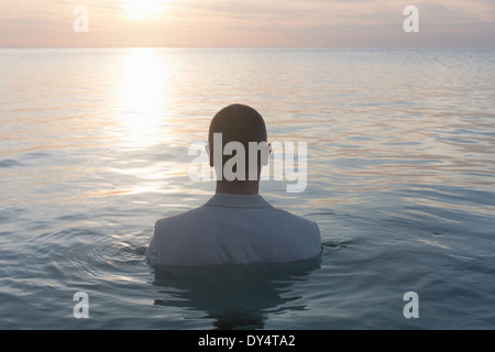 Businessperson standing in sea, rear view - Stock Photo