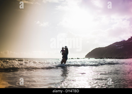 Mother holding daughter, paddling in sea - Stock Photo