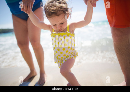Toddler and grandparents holding hands, walking on beach - Stock Photo