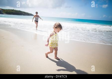 Toddler walking on beach - Stock Photo