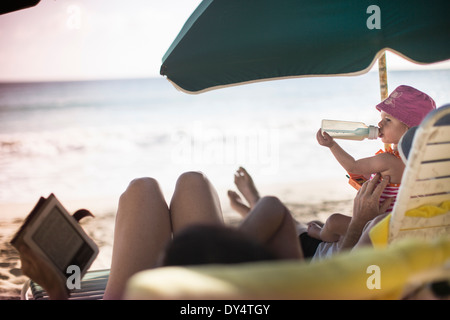 Family lying on sun loungers, reading and having a drink - Stock Photo