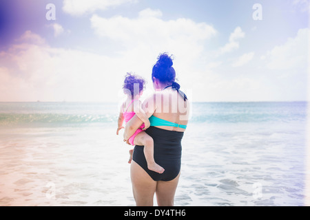 Rear view of mother and daughter looking out to sea - Stock Photo
