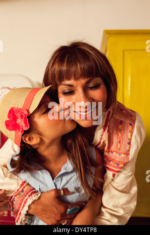 Daughter wearing straw hat kissing mother on cheek - Stock Photo