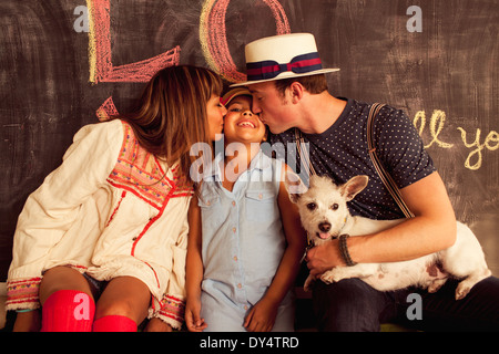 Father and mother kissing daughter on cheek - Stock Photo