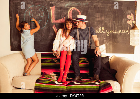 Girl drawing face on blackboard, parents on sofa - Stock Photo