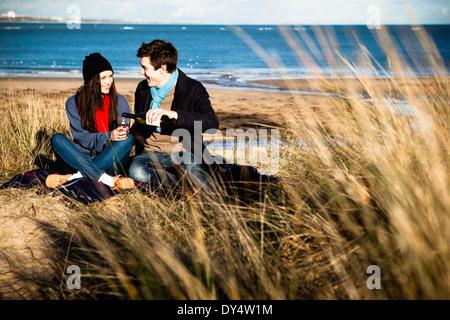 Couple celebrating with white wine on beach, Bournemouth, Dorset, UK - Stock Photo