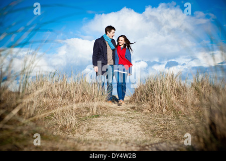 Couple walking in sand dunes, Bournemouth, Dorset, UK - Stock Photo