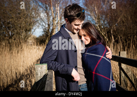 Romantic couple standing on footbridge - Stock Photo