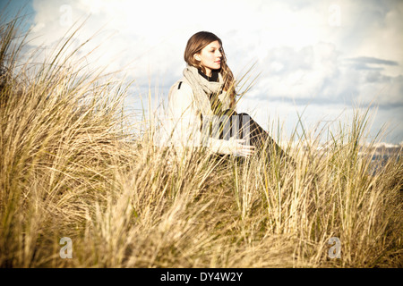 Young woman sitting in sand dunes, Bournemouth, Dorset, UK - Stock Photo
