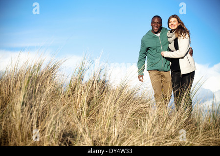 Young couple strolling in sand dunes, Bournemouth, Dorset, UK - Stock Photo