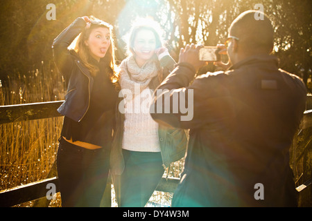 Young man photographing female friends - Stock Photo