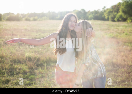 Two young women with long hair in field - Stock Photo