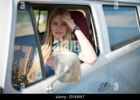 Portrait of young woman in campervan - Stock Photo
