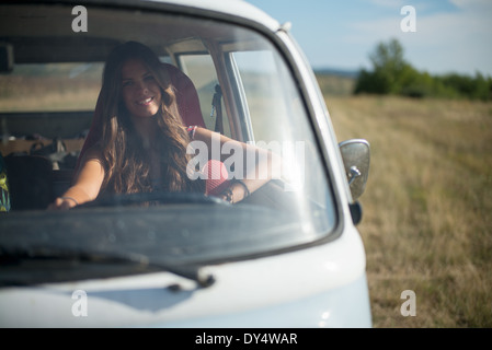 Young woman in campervan - Stock Photo