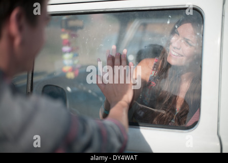 Young woman inside vehicle, man touching window - Stock Photo
