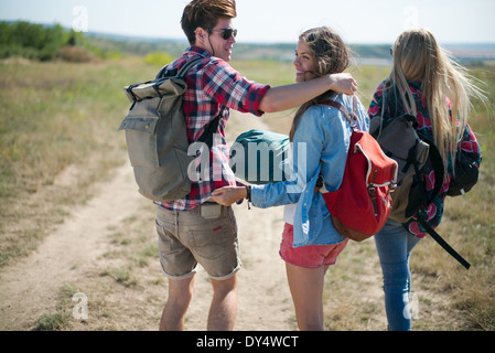 Three friends walking on dirt track with backpacks - Stock Photo