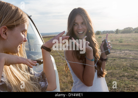 Young women listening to music on smartphone - Stock Photo