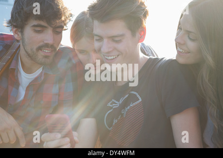 Four friends looking at smartphone - Stock Photo