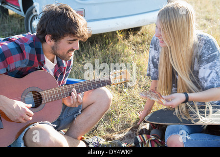 Young man playing guitar for young woman - Stock Photo