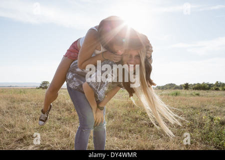 Young woman giving friend piggy back - Stock Photo
