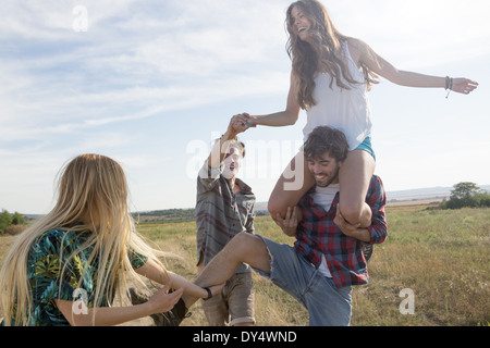Four friends playing, man carrying woman on shoulders - Stock Photo