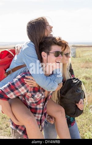 Three friends out hiking, man giving woman piggy back - Stock Photo