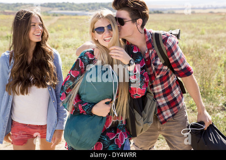 Three friends out hiking, man kissing woman - Stock Photo