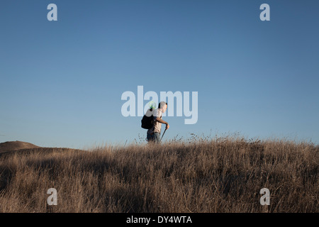 Distant view of mature man hiking in hills and long grass - Stock Photo