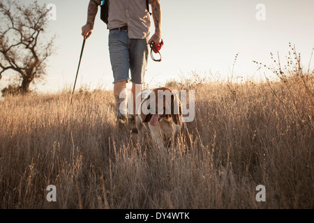 Cropped shot of mature man and his basset hound hiking in Santa Monica Mountains, California, USA - Stock Photo
