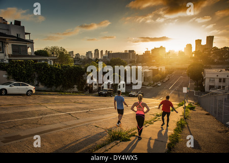 Team of runners running down a steep city hill - Stock Photo