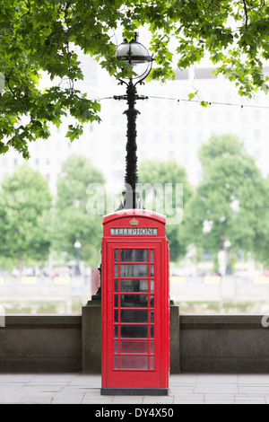 Traditional red telephone box on Embankment, London, UK - Stock Photo