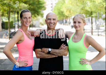 Portrait of two young women and trainer in park - Stock Photo