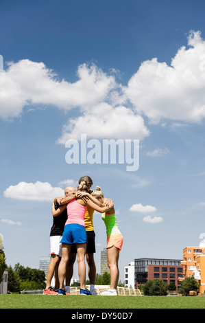 Exercise group huddled together in park - Stock Photo