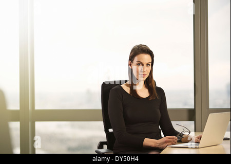 Portrait of young businesswoman sitting at office desk - Stock Photo