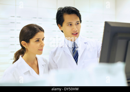 Pharmacists working on computer in pharmacy - Stock Photo