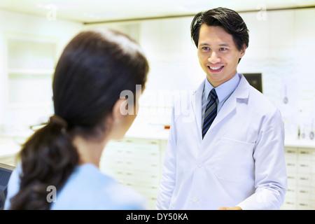 Male pharmacist handing prescription to customer - Stock Photo