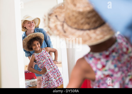 Mother and daughter looking in mirror wearing sunhats - Stock Photo