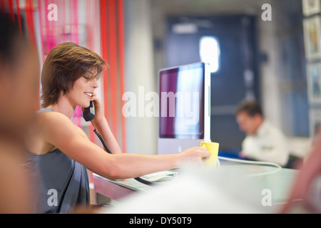 Young businesswoman using telephone in office - Stock Photo