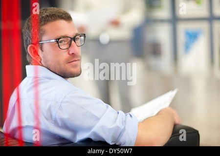 Young businessman sitting in office with paperwork - Stock Photo