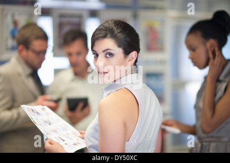 Young businesswoman looking over her shoulder in meeting - Stock Photo