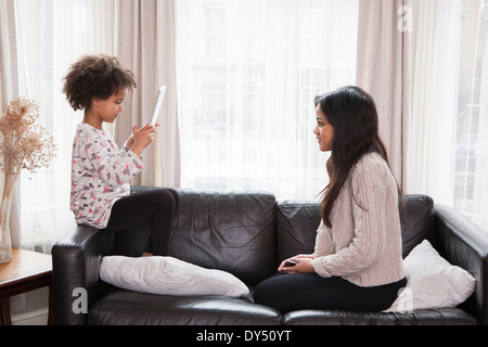 Young girl taking photograph of teenage sister on digital tablet - Stock Photo