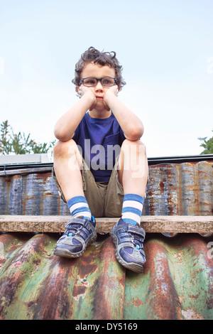 Glum little boy sitting on roof - Stock Photo