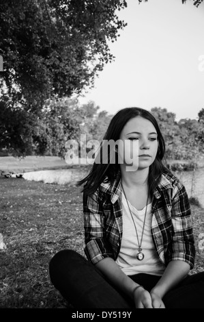 Young woman sitting on grass - Stock Photo
