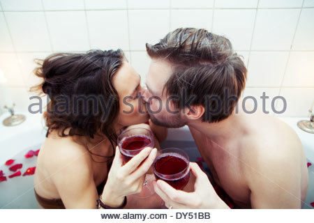 young couple in bath kissing holding wine glasses stock photo