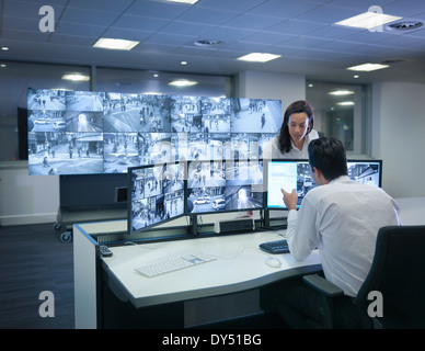 Security guards working at CCTV screens in control room - Stock Photo