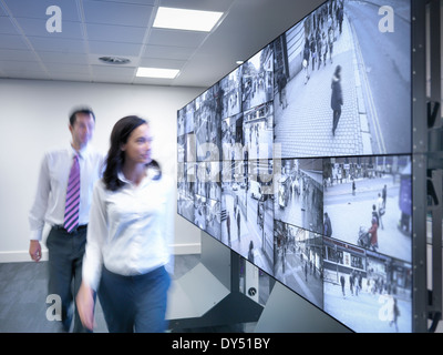 Security workers walking past CCTV screens in control room - Stock Photo