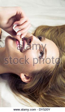 Young woman biting fingernail, close up - Stock Photo