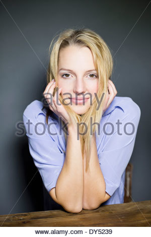 Young blonde woman leaning on elbows - Stock Photo